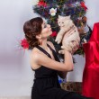 Beautiful sexy happy smiling young woman in evening dress with bright makeup with red lipstick, sitting by the Christmas tree with a small kitten in her arms in a festive Christmas evening — Stock Photo #60544463