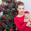 Beautiful sexy happy smiling young woman in evening dress with bright makeup with red lipstick, sitting by the Christmas tree with a small kitten in her arms in a festive Christmas evening — Stockfoto #60616529