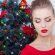 Beautiful sexy happy smiling young woman in evening dress with bright makeup with red lipstick sitting near the Christmas tree in a festive Christmas evening — Stock Photo #60616539