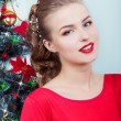 Beautiful sexy happy smiling young woman in evening dress with bright makeup with red lipstick sitting near the Christmas tree in a festive Christmas evening — Stock Photo #60616607