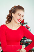 Beautiful sexy happy smiling young woman in evening dress with bright makeup with red lipstick sitting near the Christmas tree in a festive Christmas evening — Stock Photo