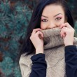 Beautiful young happy woman winter day in the forest near trees hides his face under jacket — Stock Photo #60958999
