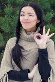 年轻漂亮的幸福女人眨眨眼和显示像树木附近的森林中的确定冬季的一天 — 图库照片