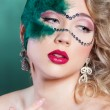 The beautiful young woman in a green mysterious venetian mask a new year carnival, Christmas masquerade, a dance club, secret night party, with beautiful makeup — Stock Photo #61421557