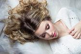 Mooi lachende gelukkig meisje met lichte make-up ligt op het bed met bont in witte trui — Stockfoto