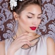 Beautiful young elegant girl with bright makeup with red lips with a beautiful wedding hairstyle for the bride with white flowers in her hair, stylish way — Stock Photo #67096209