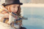 Retro portret beautiful young sad girl in hat and coat stands on the dock, looking at the blue sea on a Sunny day at dawn — Foto de Stock