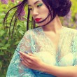 Chinese beautiful sexy girl in a kimono with a beautiful makeup with hair walking in a garden near blooming lilac bushes — Stock Photo #73318773