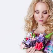Beautiful sexy modest sweet tender girl with curly blond hair standing on white background with a bouquet of flowers of lavender in blue summer dress — Stock Photo