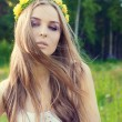 Beautiful sexy sweet girl with long hair and a wreath of yellow roses on his head in the field, the wind blowing her hair — Stock Photo #75931993