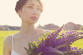 Beautiful sexy girl with a sweet lupine flowers with beautiful hair in a white sundress standing in a field at sunset in the warm summer sun — Stock Photo