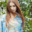 Beautiful sexy cute sweet girl with long red hair and green eyes in a denim jacket near a flowering tree in the park the wind blowing her hair — Stock Photo #76163389