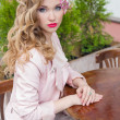Beautiful sweet girl with hair and make-up color bright sitting at a table at an outdoor cafe and waiting for your order — Stockfoto #76329825