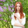 Beautiful sexy cute red-haired girl in a white dress standing near bushes with lilac — Stock Photo #76329851