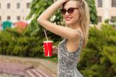 Beautiful sexy cute happy smiling girl with a glass in his hand in sunglasses drinking a Coke on a sunny hot day — Stock Photo