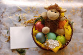 Easter lamb with colored pearly eggs in basket — Zdjęcie stockowe