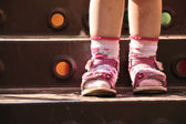 Baby legs in shoes and socks, standing on step of stairs — Stock Photo