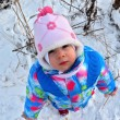 Small child looks up at winter snowy landscape — Stock Photo #80659214