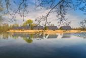 Solar panels bask in the sun over a Cotswold lake — Stock Photo