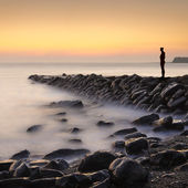 Lone figure stands looking out to sea — Stock Photo