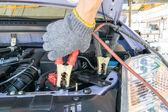 Automotive technician charging vehicle battery — Stock Photo