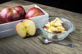 Rode appels in de kom en appels in het vak op de houten tafel — Stockfoto