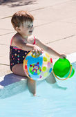 Baby playing in swimming pool water — Stock Photo