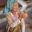 Elderly woman burnese smokes a cigar in his traditional house in a village of Bagan — Stock Photo #73199653