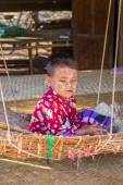 Child in a hanging basket in its traditional home in a village of Bagan, Myanmar — Stock Photo