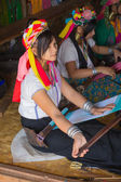 Girl of the tribe Kayan (Padaung) in traditional clothing works to weaving cotton in his village near Lake Inle — Stock Photo
