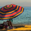 Woman under parasol on the beach — Stock Photo #52686513