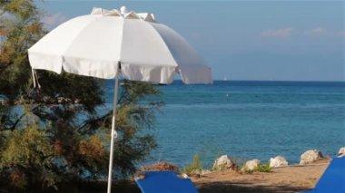 Branco guarda-sol e espreguiçadeiras na praia, grécia — Vídeo Stock