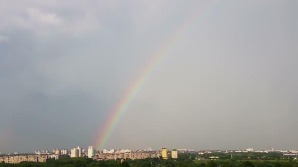 Grandes arco iris encima de edificios de la ciudad. Lapso de tiempo. — Vídeo de stock