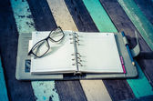 A notebook and glasses — Stock Photo