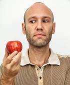 Man questioningly looking at red apple — Stock Photo