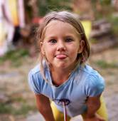 Little girl teases and puts out her tongue — Stock Photo