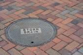Storm Drain Cover on a Brick Road — Stock Photo