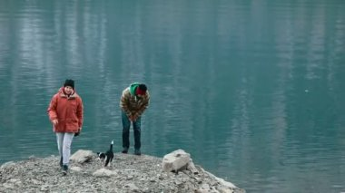 The couple playing with dog on the shore of the lake, Altay — Stock Video