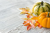 Pumpkins on wooden background with autumn leaves — Stock Photo