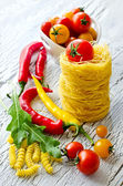 Italian pasta nest with cherry tomatoes, chili and rucola — Stock Photo