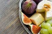 Brie, figs and grapes on a tray copy space — Stock Photo