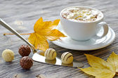 Pralines, a cup of cappuccino and autumn leaves — Stock Photo
