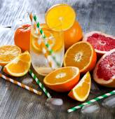 Fresh orange and grapefruits with glass of water and straws squa — Stock Photo