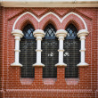 Red brick wall and stained glass window in Holy trinity Cathedral in Yangon, Myanmar, Burma — Stock Photo #71790867