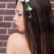 Beauty face of the young beautiful woman with white flowers in her hair. Fashion model with hairstyle and flowers in her hair — Stock Photo #69658495