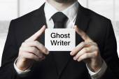 Businessman holding sign ghost writer — Photo