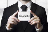 Businessman holding sign biography — Stock Photo