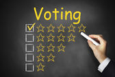 Hand writing voting on chalkboard — Stock Photo