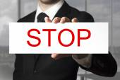 Businessman holding sign stop — Stock Photo