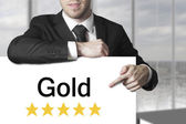 Businessman pointing on sign gold — Stock Photo